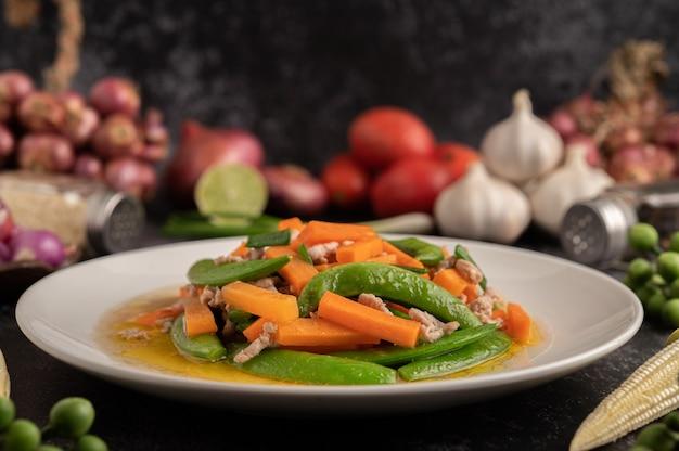 Misture as ervilhas fritas e as cenouras de porco picadas em um prato branco.