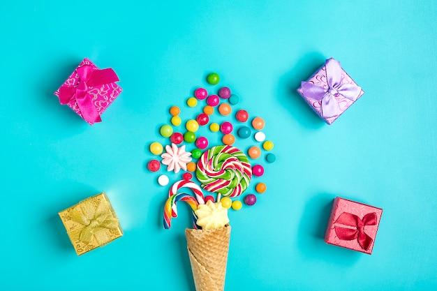 Misture doces de chocolate coloridos derramados fora do cone de waffle de sorvete, caixas de presente na configuração plana azul