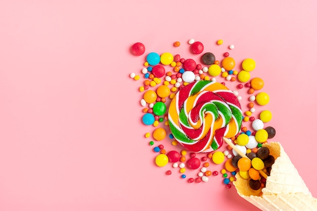 Misture doces de chocolate coloridos derramados fora do cone de waffle de sorvete no leigo rosa plana