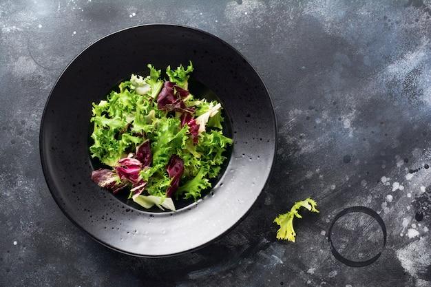 Misture folhas frescas de rúcula, alface, espinafre, beterraba para salada em um fundo de pedra escuro. foco seletivo.
