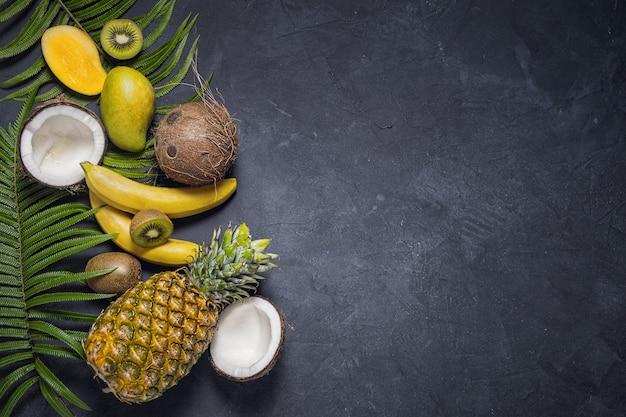 Misture frutas tropicais em fundo escuro, vista superior. conceito de alimentação, nutrição e dieta saudável