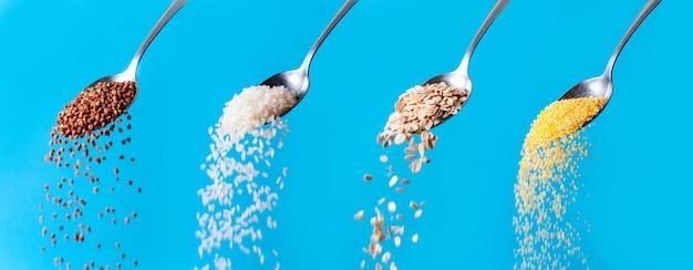 Misture grãos de cereais orgânicos. sementes de trigo mourisco cru, aveia, arroz, flocos de grãos de milho caindo das colheres sobre fundo azul