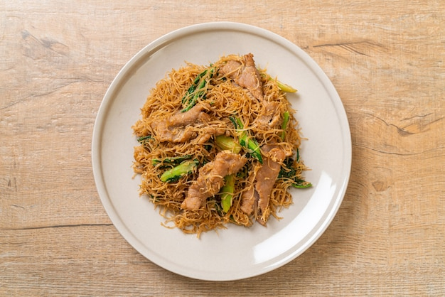 Misture macarrão de aletria de arroz frito com molho de soja preto e carne de porco - estilo de comida asiática