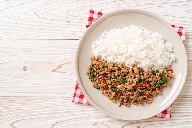 Misture manjericão tailandês frito com carne de porco picada e pimenta malagueta no arroz coberto - comida local tailandesa