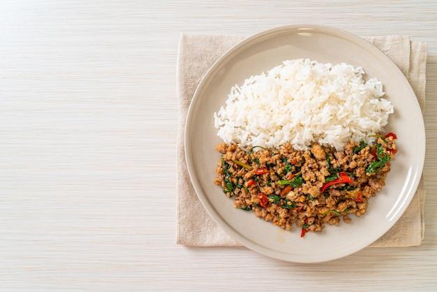 Misture manjericão tailandês frito com carne de porco picada e pimenta no arroz coberto - estilo de comida local tailandesa