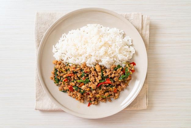 Misture manjericão tailandês frito com carne de porco picada e pimenta no arroz com cobertura, ao estilo da comida tailandesa local