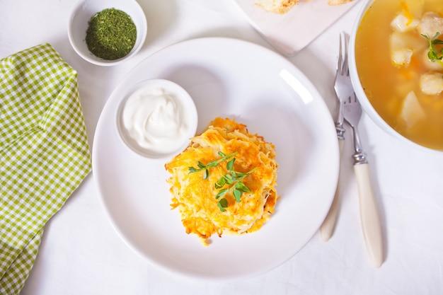 Misture o draniki das panquecas de batata dos marrons na placa branca. café da manhã.