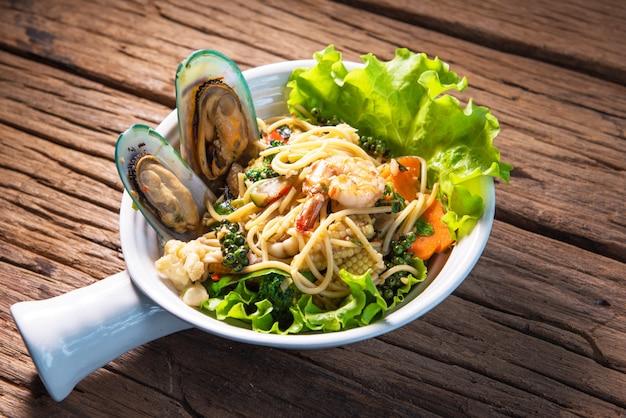 Misture o espaguete frito com frutos do mar, coloque em uma xícara de terracota bonita e coloque sobre uma mesa de madeira.