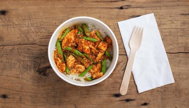 Misture o frango frito com vegetais em uma caixa de papel para alimentos