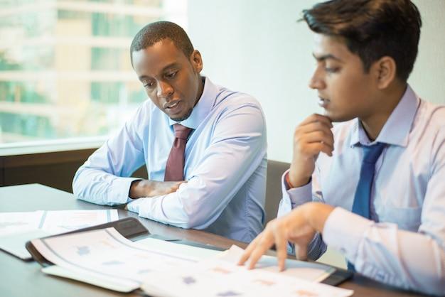 Misture o grupo de negócios corrido analisando relatórios