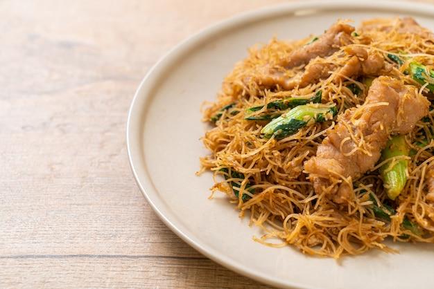 Misture o macarrão de aletria de arroz frito com molho de soja preto e carne de porco
