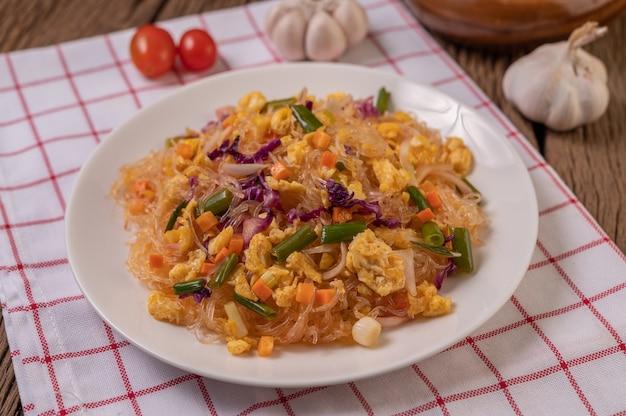 Misture o macarrão de vidro frito com os ovos e coloque em um prato sobre um pano branco vermelho.