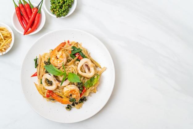 Misture o macarrão picante frito com frutos do mar e ingredientes