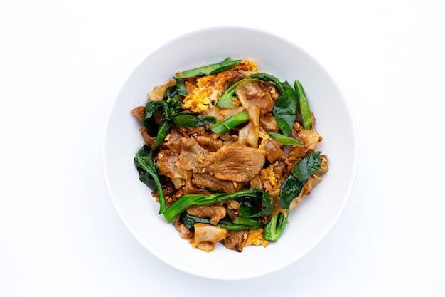 Misture o macarrão plano frito e a carne de porco com molho de soja.