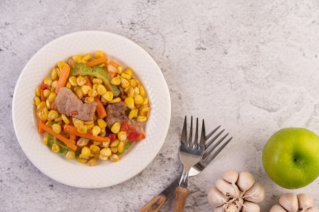 Misture o milho e as cenouras, coloque a carne de porco no prato de madeira.