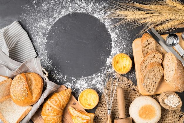Misture o pão, croissant, baguete, bolinho e egg tart no fundo de pedra preta, vista superior e spa de cópia