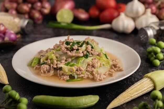 Misture o repolho chinês frito com carne de porco picada no prato branco.