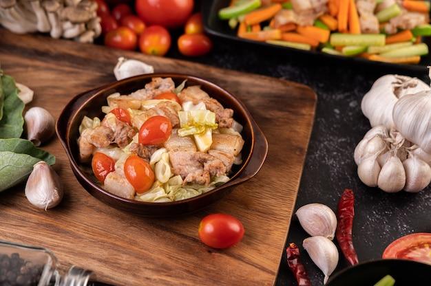 Misture o repolho com barriga de porco em um prato sobre uma placa de madeira.