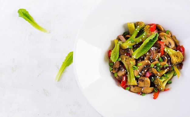 Misture os vegetais fritos com os cogumelos, páprica, cebola roxa e brócolis. comida saudável. cozinha asiática. vista superior, sobrecarga