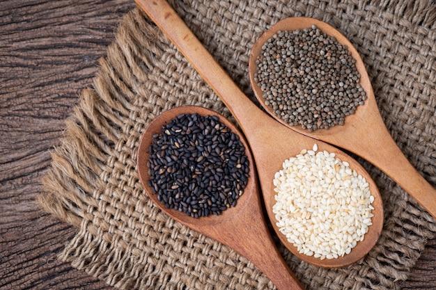 Misture sementes de gergelim na mesa de madeira.