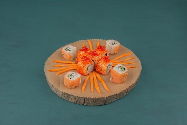 Misture sushi com rodelas de cenoura na placa de madeira.