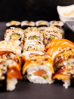 Misture vários rolos de sushi em fundo de pedra preta em estúdio