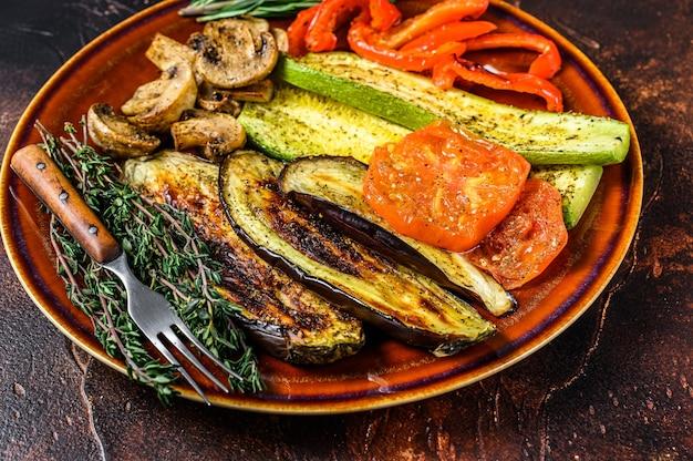 Misture vegetais grelhados em um prato rústico. fundo escuro. vista do topo.