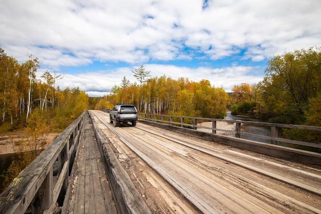 Mitsubishi pajero sport em ponte de madeira na floresta de outono