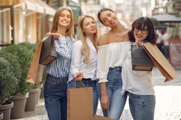 Miúdas giras com sacola de compras em uma cidade