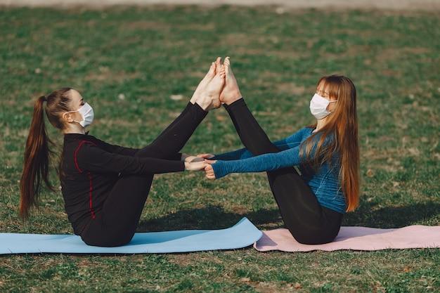 Miúdas giras fazendo ioga em uma máscara