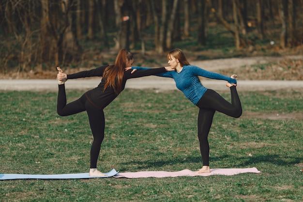Miúdas giras fazendo yoga em um parque de verão