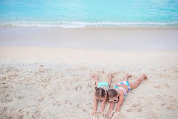 Miúdas giras na praia arenosa. feliz, crianças, mentindo, ligado, morno, branca, praia arenosa