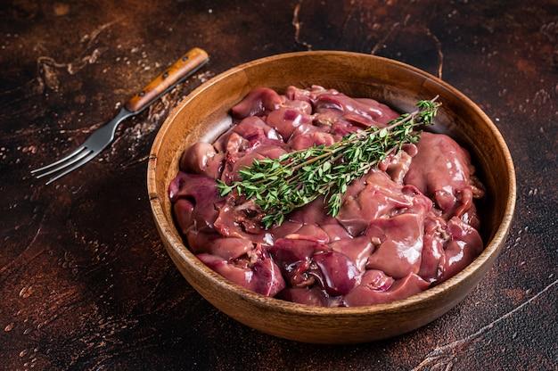 Miudezas de fígado de frango cru em um prato de madeira