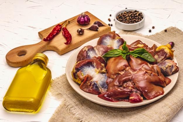 Miudezas de frango cru fresco: coração, fígado, estômago com especiarias secas, sal marinho, pimenta, azeite, hortelã fresca sobre fundo branco massa