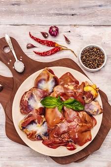 Miudezas de frango cru fresco: coração, fígado, estômago com especiarias secas, sal marinho, pimenta na mesa de madeira