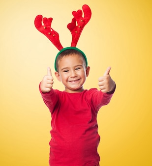 Miúdo alegre com uma cabeça renas e polegares para cima