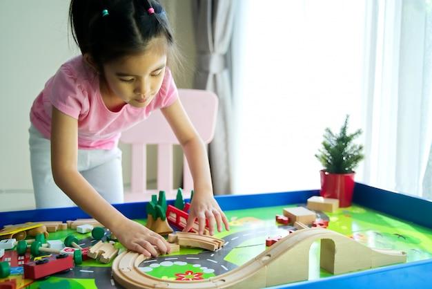 Miúdo bonito asiático pequeno novo que joga o brinquedo de madeira na tabela em casa.