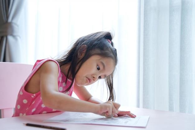 Miúdo bonito da menina asiática que usa o eliminador no papel para apagar o que tinha escrito.