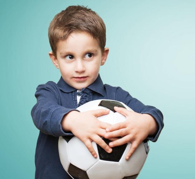 Miúdo bonito segurando uma bola de