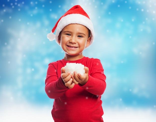Miúdo de sorriso com neve em suas mãos