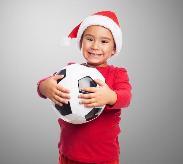 Miúdo de sorriso querendo jogar futebol
