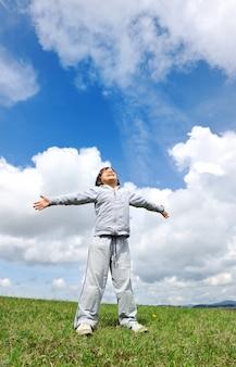 Miúdo em ar fresco na natureza com fundo de céu e nuvens