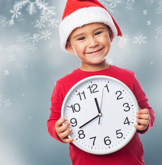 Miúdo feliz segurando um relógio grande