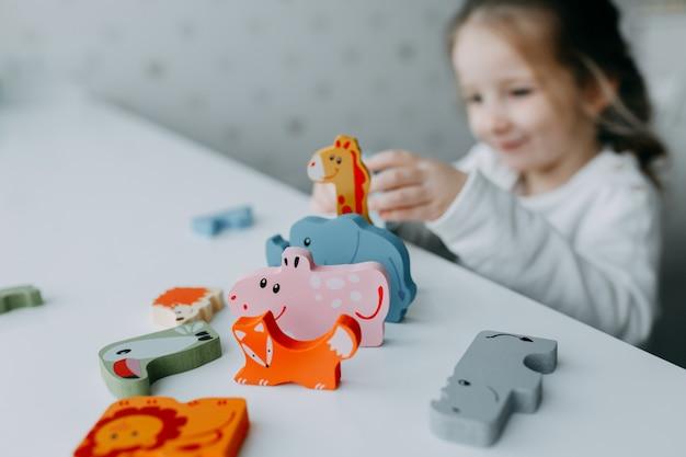 Miúdo giro brincar com animais de brinquedo como girafa e coala
