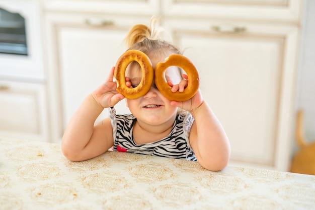 Miúdo pequeno da criança que tem o almoço na cozinha ensolarada morna. menina loira com rabo de cavalo engraçado brincar com dois bagels saborosos