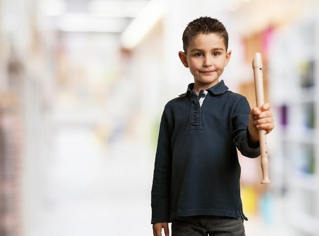 Miúdo que levanta com uma flauta