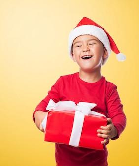 Miúdo que ri ao prender uma caixa de presente
