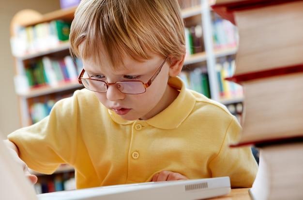 Miúdo que usa o portátil na mesa