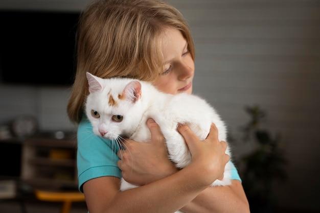 Miúdo tiro médio a abraçar o gato