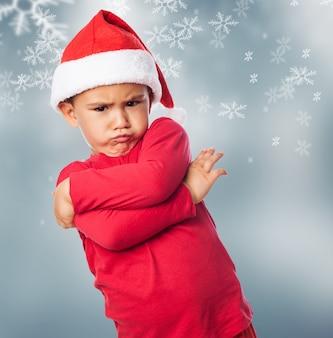 Miúdo triste que veste o chapéu de santa com flocos de neve fundo